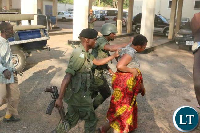 A female UPND supporter being handled by police officers