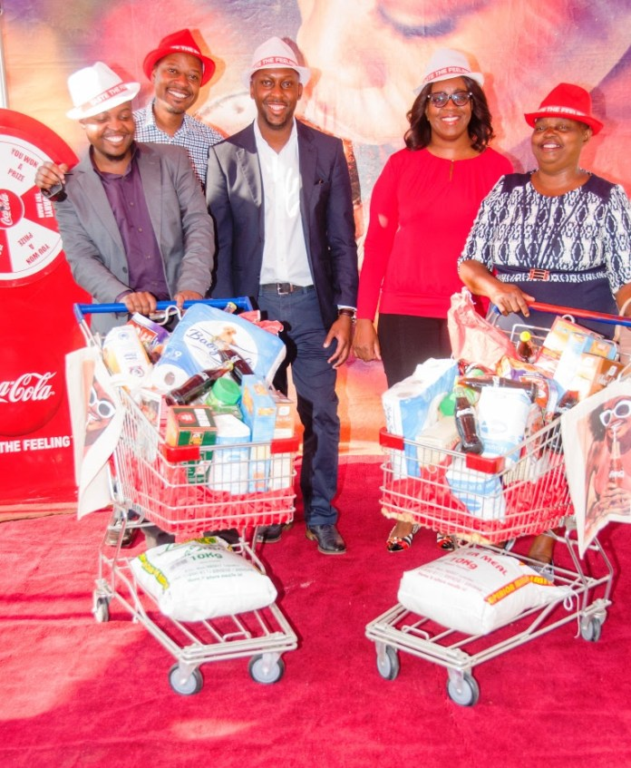 Coca-Cola Marketing Activations Manager for Zambia and, Malawi, Takunda Jinda, Zambian Breweries Marketing Manager Mambo Mwiimbu (centre), and Coca-Cola Operations Marketing Manager for Zambia Makusi Makani, with trolley dash launch winners journalist Limbikani Msambe and wholesaler Gladys Nyeleti.