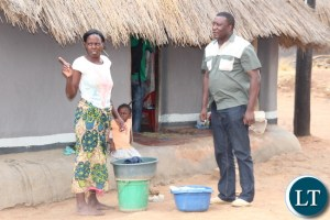 Zesco spokesperson Henry Kapata talking to Sarah Tembo, a beneficiary of newlyelectrified thatched house in Luangeni village in Chipata DistrictEastern Province. Picture by Jean Mandela