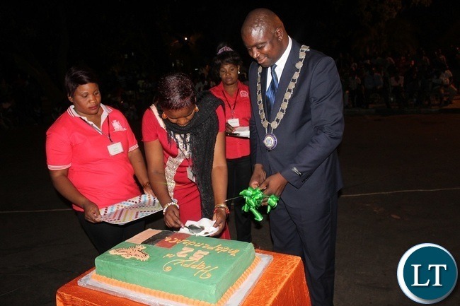 Livingstone Mayor Eugene Mapuwo (right) being assisted to cut the cake during the eve of Zambia's 52nd independence celebrations in Livingstone on Sunday. Picture by KELVIN MUDENDA