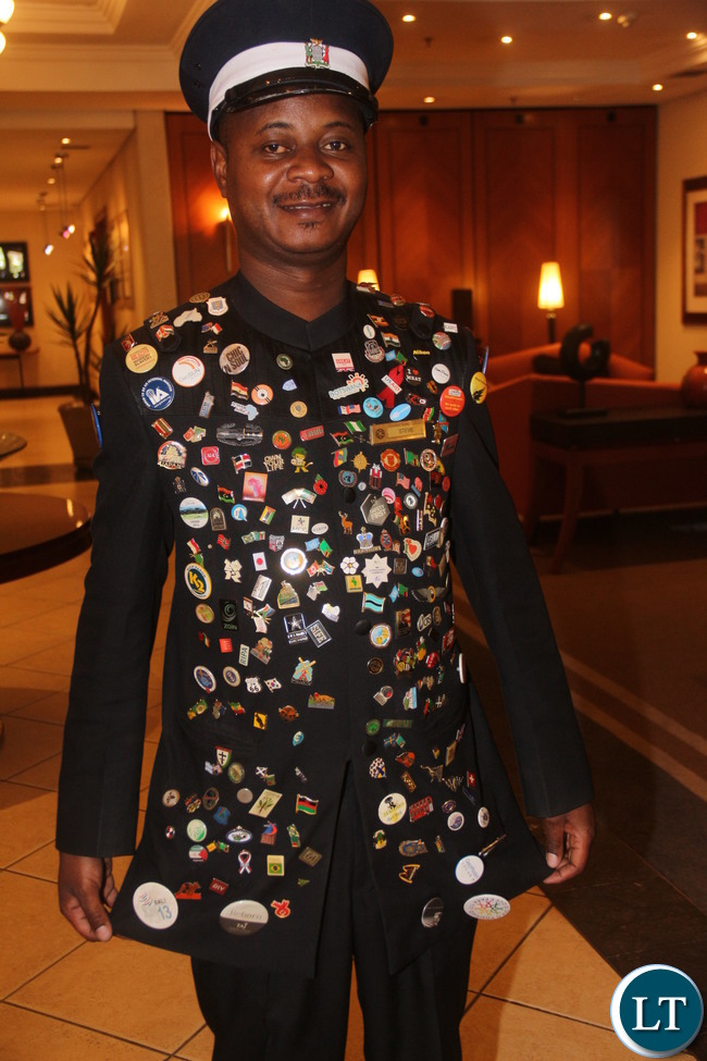 Taj Pamodzi Hotel Bellman Steve Ndombe displaying his jacket, a collection of more than 200 pins that he has been collecting for the past 3 years