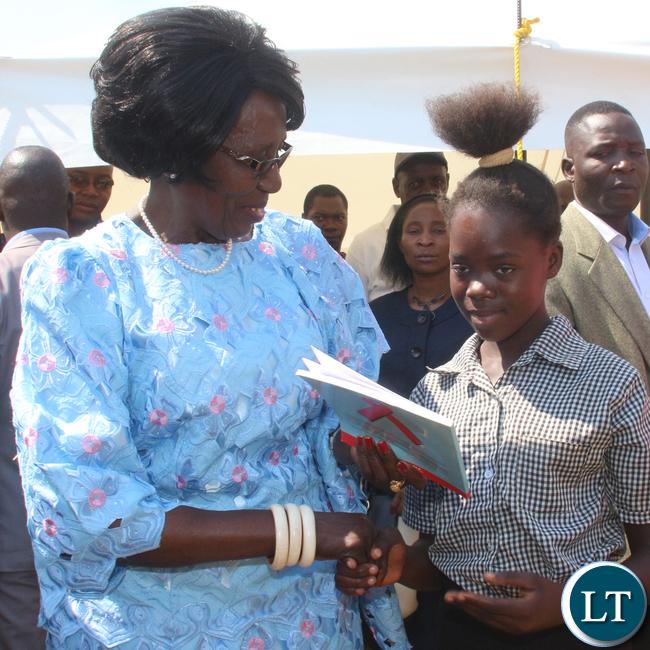 Zambia VEEP Inonge Mutukwa Wina presenting a book sample of her donation to a school pupil