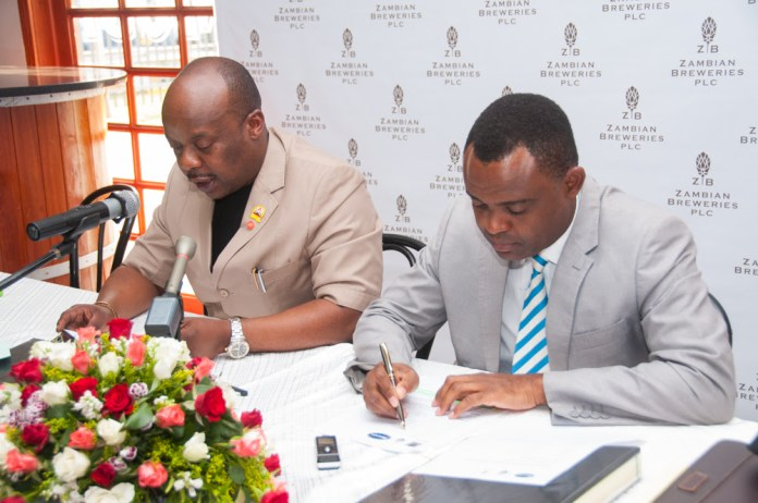 RTSA Chief Executive Officer Zindaba Soko, left, and Zambian Breweries Corporate Affairs Director Ezekiel Sekele sign an MOU on road safety.
