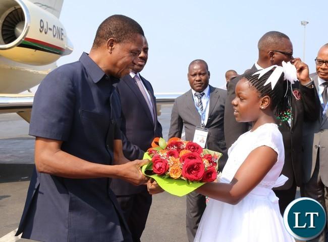 President Edgar Lungu receives a bouquet from a 10 year old Lukundo Nachilongo at Luanda international airpot in Angola 26-10-2016