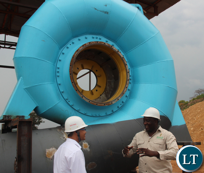 Sinohydro project Manager Mr Ying Feng Zeng shows Zesco spokesperson Henry Kapata the new turbine to be installed at the new Musonda Falls Power station. The Musonda falls power station is being upgraded from 5 to 10 Mega Watts. Picture By Jean Mandela