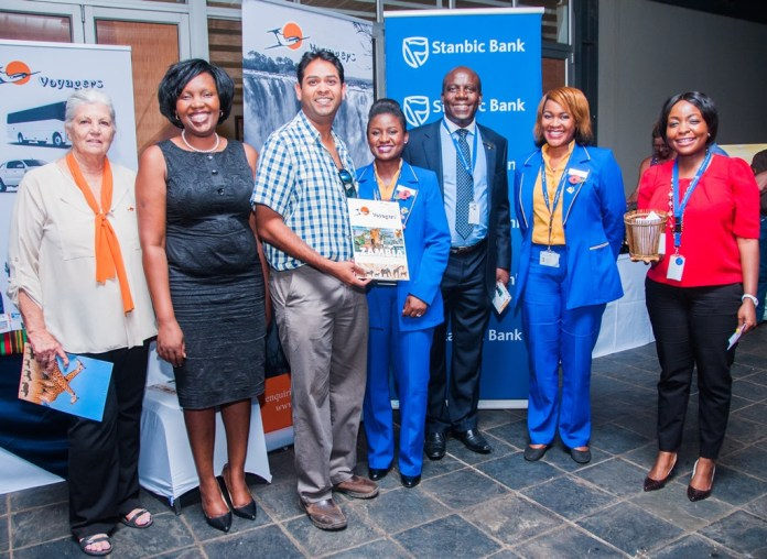 Proflight Marketing Manager Hellen Ngwira Mwamba, second right, and Commercial Development Analyst Mwate Van-Rietvelde, centre, with draw winner Andre Tennekoon, centre, along with Stanbic Bank Zambia Chief executive Charles Mudiwa, third right, Stanbic Head of Personal and Business Banking Mukwandi Chibeskunda, second left, Voyagers Manager Molly Care, left, and Stanbic Public Relations and Communications Manager Chanda Chime-Katongo, right.
