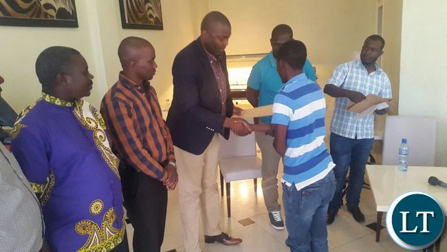 Copperbelt Minister Bowman Lusambo hands over scholarship to Charles Tembo