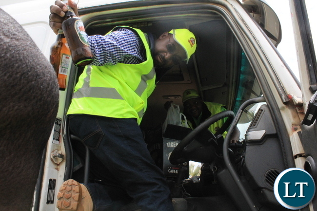 MINISTER of Transport and Communications Brian Mushimba removes bottles of Mosi lager beer from the drivers porch at check point mounted by the Road Transport and Safety Agency, in Mazabuka on Sunday morning. Mr Mushimba has been physically involved in the enforcement and compliance of motor vehicle and road safety regulations. The driver of the fuel tanker was found drunk and was later detained and charged for breaking the law.. PICTURE: BRIAN MALAMA
