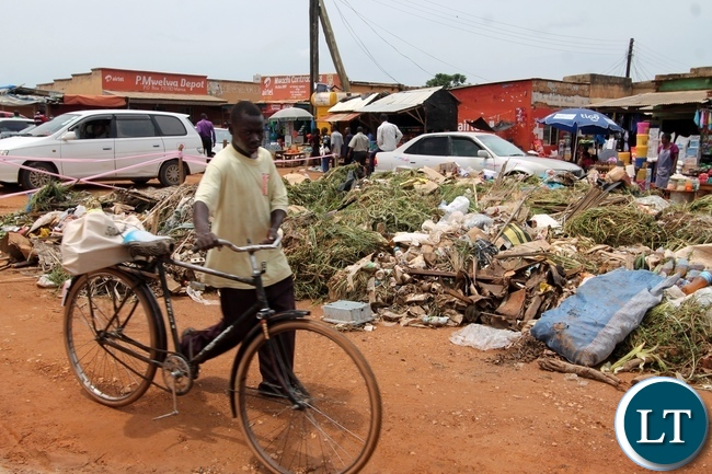 A cyclist passing through uncollected garbage at UB Market in Mansa Town.