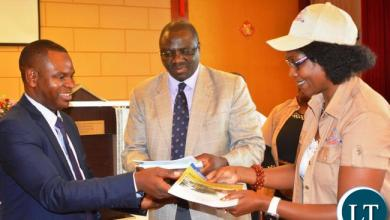 General Nursing Council President Dr. Lonia Mwape(r) and General Nursing Council Registrar Aaron Banda(l) presenting the 2016-2020 Strategic Plan to the Ministry of Health Permanent Secretary Dr. Jabbin Mulwanda(c) during the official launch of the General Nursing Council Strategic Plan