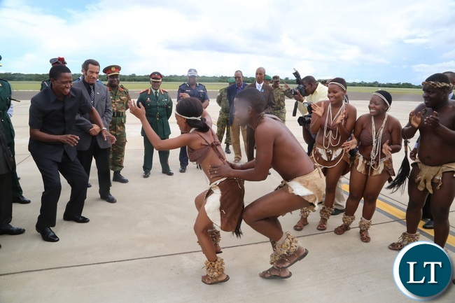 President Edgar Lungu joins in Matsosangwao traditional arts group as Botswana President Ian Khama (r) looks on shortly after his arrival at Kasane Airport