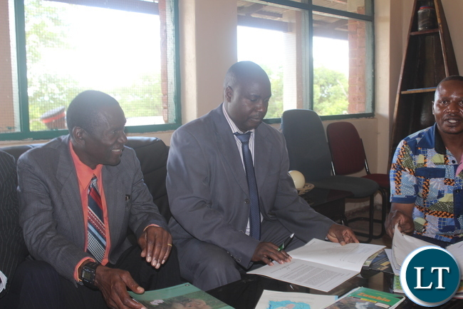 Southern Province Minister Dr Edify Hamukale (Right) signs the visitors' book at the refurbished Lochnivar National Park Guest House. This was during his tour of the National Park