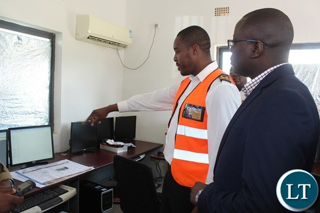 ZAMBIA Revenue Authority (ZRA) Assistant Customs Officer, Allan Chila, shows Eastern Province Minister, Makebi Zulu, scanner monitors during the inspection of the scanning facility at Chanida border post on Tuesday. PICTURE BY STEPHEN MUKOBEKO/ZANIS