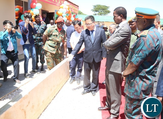 Shandong Dejian Group General Manager Huang Meng shows President Edgar Lungu the Material they are using when building during the Launch of the Construction of Zambia National Service (ZNS) Housing Units in Chamba Valley yesterday 30-03-2017 Picture by ROYD SIBAJENE/ZANIS