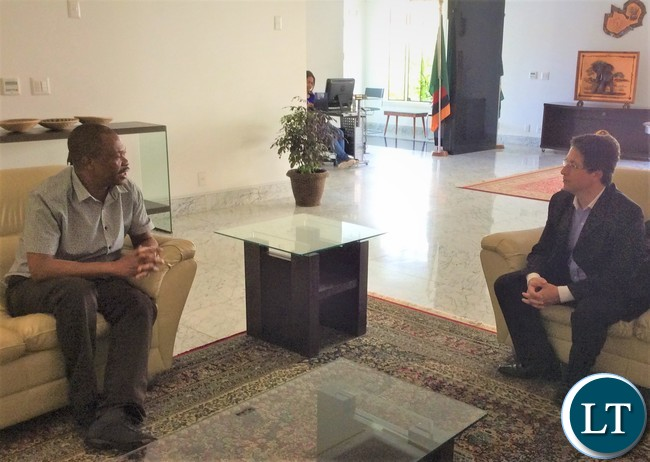 Defence Advisor at the Zambian Mission in Brasilia Colonel Godwin Chenda chatting with Embraer Sales Engineering Manager Mr. Gustavo Siqueira when he passed through the Chancery to collect the Visa for Zambia.