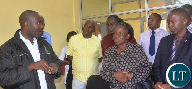 Senior Meteorological Officer Victor Bupe explains to Ministry of transport and communication Human Resources Director Bridget Mukuyamba with Meteorological Acting Director Joseph Kanyaga how to conduct the weather focus at meteorological department during the tour in Lusaka