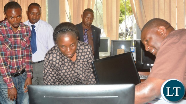 Ministry of transport and communication Human Resources Director Bridget Mukuyamba looks at weather focus monitor during the tour in Lusaka
