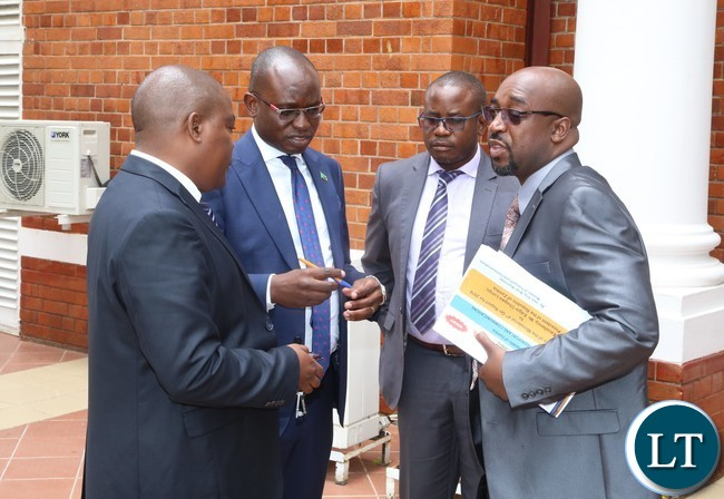 Special Assistant to th President for Press Amos Chanda (2nl) Minister of Transport and communication Brain Mushimba (r) Public Relations Officer Ministry of Transport and Communication Brain Malama (2nr) and Permanent Secretary Ministry of Transport and Communication Misheck Lungu chat shortly after the presentation of the quarterly report 2016 at State House
