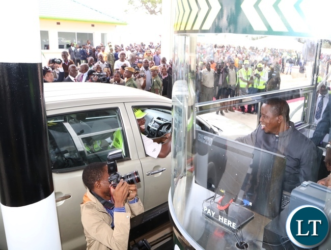 President Edgar Lungu demonstrates on how they work at the Katuba Toll Plaza booth during the Commissions of the Plaza in Katuba