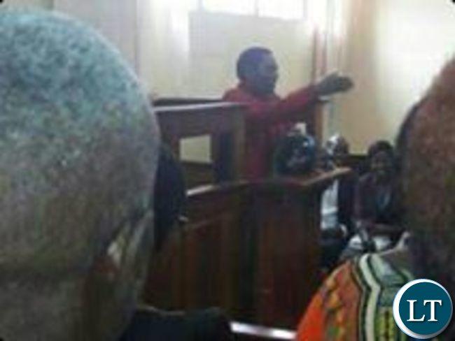 Hakainde Hichilema gestures the UPND symbol in the dock