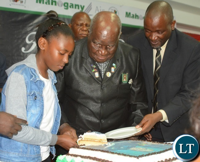 First Republican President Kenneth Kaunda(c),his granddaughter Sonji(l) and Minister of Water and Sanitation Loyd Kaziya(r) cutting the cake during Zambia Association of Musician KK's Birthday Bash in Chongwe