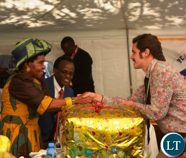 Peace Corp Volunteer Dylon Scott Taylor(r) presents a gift of appreciation to Her Royal Highness Senior Chieftainess  Nkomeshya Mukamambo II(l)  at the Peace Corps Swearing in Ceremony for Environment and Aqua-Culture Volunteers in Lusaka