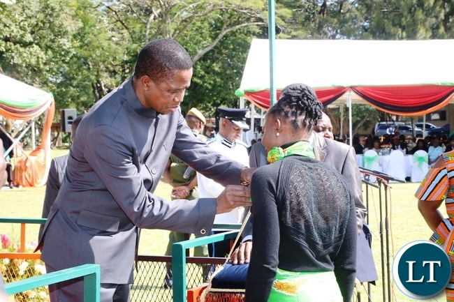 President Edgar Lungu gives a medal of Zambia Insignia of Meritorious achievement award to Catherine Phiri William Nkanza during the Africa Freedom Day at State House