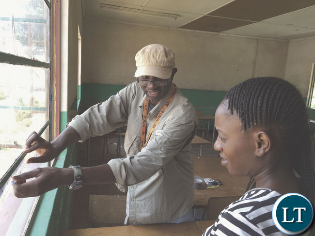 Dr Samuel Mutiti shows his research assistant how to collect dust samples from a school window in Kabwe, Zambia
