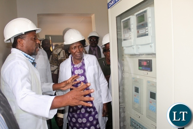 Rural Electrification Authority (REA) Site Manager Eng. Daniel Kapambwe (l) explains to Vice President Inonge Wina (c) inside the sub-station during the commissioning of the connection of Luampa District to the National Grid through REA at twenty million Kwacha (K20, 000, 000) in Western Province