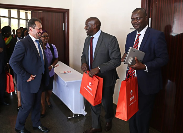 Airtel Chief Executive Officer Peter Correia confers with Ministry of Transport and Communication Director Communication Jese Bwalya (r) and ZICTA Managing Director Patrick Mutimushi (2nr) shortly after the launch of Airtel 4G network at Raddison Blu