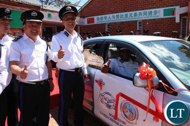 Zambia Police IG Kakoma Kanganji testing one of the cars handed over while looking on are Zambia Police reserve Senior Superintendent Wu Ming (far left) and Zambia Police reserve Assistant Commissioner Zhang Ming (next to the IG)