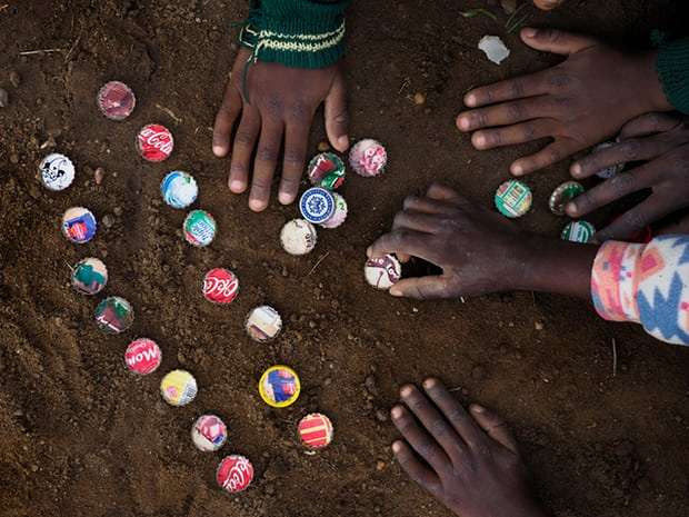 Children playing with bottle tops in the dust in Chowa township in Kabwe. The dust is highly contaminated with lead, which is extremely toxic. Photograph: Larry C Price for the Guardian