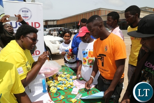 Mercy Bulaya explains on how to use the condom to people during the International Condom Day tour of stands at Central Mall