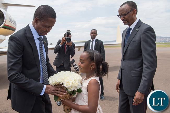 President Edgar Lungu receives a bouquet of flowers from a young girl on arrival at the Kigali International Airport, as his host, President Kagame, looks on yesterday. (Village Urugwiro)