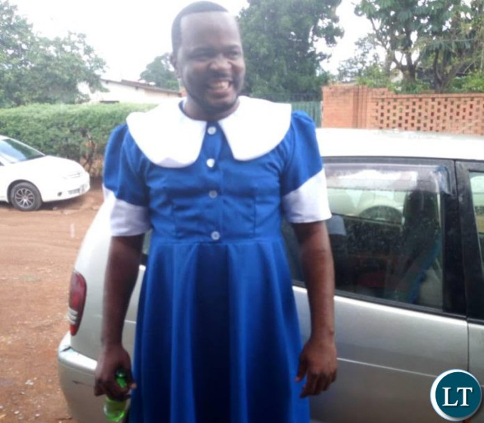 Maxwell Chongu clad in a Seventh Day Adventist (SDA) Dorcas uniform while holding a bottle of beer.