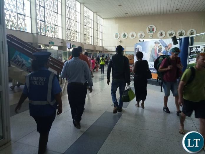 Pilato being led out of KKIA by plain clothed police officers