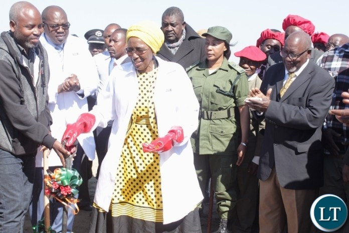Vice President Inonge Wina (c) receives a shovel to do the ground breaking as Barotse Royal Establishment (BRE) Ngambela (Prime Minister) Mwenda Nyambe (r) looks on during the ground breaking ceremony for the proposed construction site of Lealui Mini Hospital in Mongu