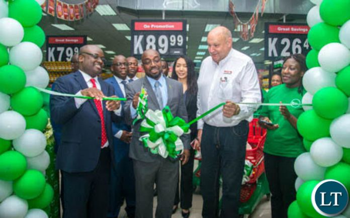 Transport and Communications Minister Brian Mushimba cuts the ribbon to launch ZamPay APP at Spar Arcades as Zamtel CEO Sydney Mupeta and Spar Zambia General Manager Ken Darvy look on