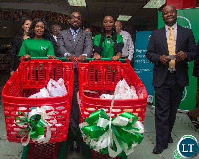 Transport and Communications Minister Brian Mushimba ready to pay for his shopping using ZamPay during the launch of the product at Spar Arcades on Tuesday