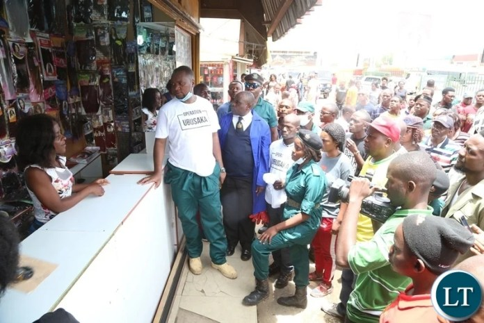 Lusaka Mayor Miles Sampa interacts with a marketeer at Samson building during the Cleaning of the Central Business District under the theme Ubusaka