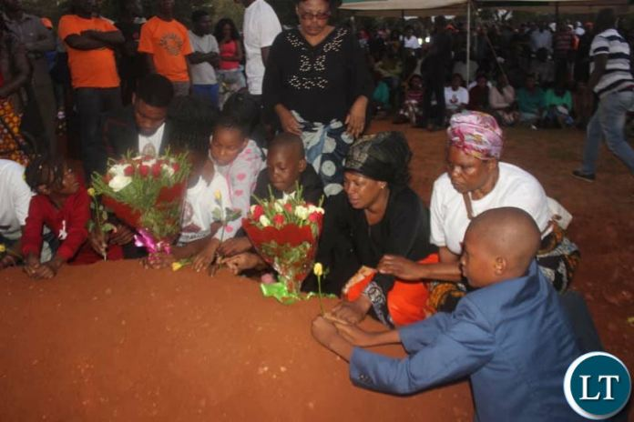 Mr Kasongo's Children and other family members lay flowers on his grave at Memorial Park.