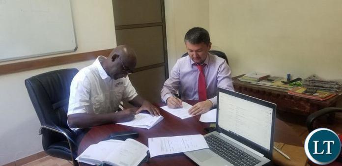 AB Bank Chief Credit Officer Nurullo Mashrabov signs the MoU with Medeem Business Development Manager Musenge Nsakilwa.