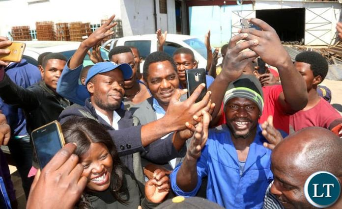 HH takes selfies with youths working in the Lusaka industrial area