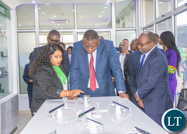 Zamtel Retail and Channels Manager Mwimba Makanta explains the functionality of the latest devices on display to IDC Group CEO Mateyo Kaluba as Zamtel CEO Sydney Mupeta looks on during the launch of the Woodlands Customer Service Centre