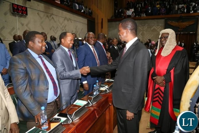 President Lungu Shaking hands with UPND Deputy Spokesperson Cornelius Mweetwa at parliament while the Speaker of the National Assembly Looks on
