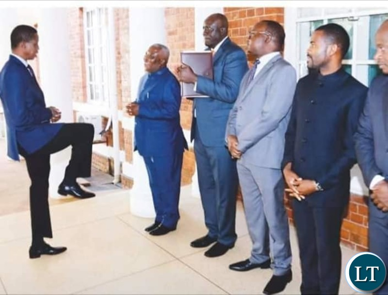President Lungu demonstrating the new way to greet to Presidential Affairs Minister Hon Feedom Chomba Sikazwe
