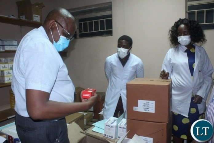 Ministry of Health Technical Services Permanent Secretary Dr. Kennedy Malama(l) going through the drugs at Mongu District Hospital Pharmacy as hospital medical officer in-charge Dr. Chilufya Musonda (c) and Pharmacist Diana Uyoya (r) look on during the tour of health facilities in Mongu