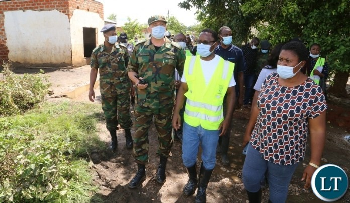 Minister in the Office of the Vice President Olipa Phiri flanked by DMMU national coordinator Chanda Kabwe and defence force officers visiting the flooded homes in Mumbwa District after the Kandesha dam burst it banks yesterday. Sunday, December 27, 2020. Picture by ROYD SIBAJENE/ZANIS