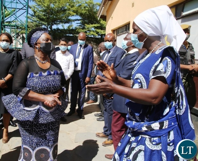 ST Kizito Parish Women Council Chairperson Mary Mukuka shares a light moment with First lady Esther Lungu when she officiated at a donation of food hampers in George Compound in Lusaka. Picture by SUNDAY BWALYA/ZANIS