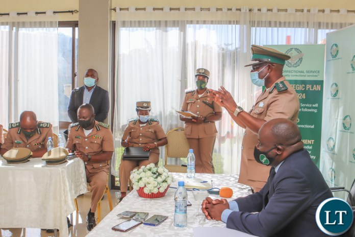 Zambia Correctional Service Commissioner General Dr Chisela Chileshe addresses members of his top command during the signing ceremony as Zamtel CEO Sydney Mupeta listens on